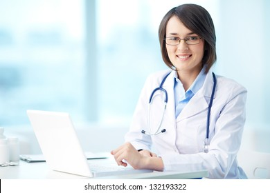 Portrait of a smiling physician working in her office