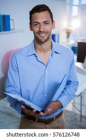 Portrait of smiling physiotherapist holding clipboard in clinic