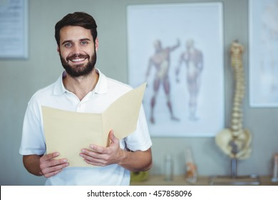 Portrait of smiling physiotherapist holding file in clinic
