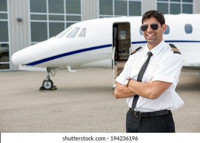 Portrait of smiling pilot with arms crossed standing in front of private jet