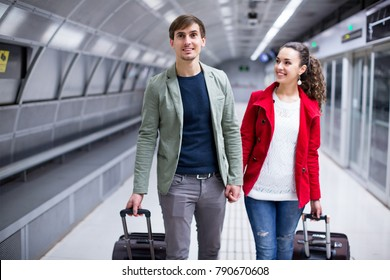 Portrait of smiling pleasant couple with wheeled trollers at subway platform
