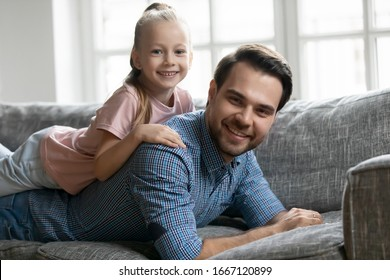 Portrait of smiling pleasant young father lying on comfy sofa, holding cute little blonde kid daughter on back. Affectionate two generations family enjoying weekend time, resting on couch at home.