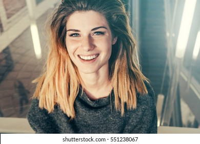 Portrait of smiling positive woman.Dental concept,white teeth.Happy girl enjoy life,neutral indoor background