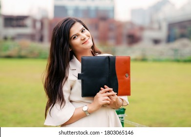 Portrait of a smiling pretty Asian/ Indian girl holding books and looking at camera.