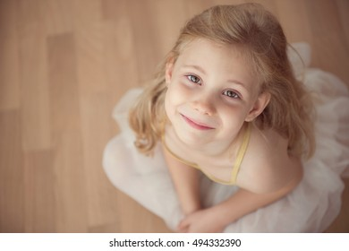 Portrait of smiling pretty diligent ballet girl sitting in white tutu at dance studio. View from above