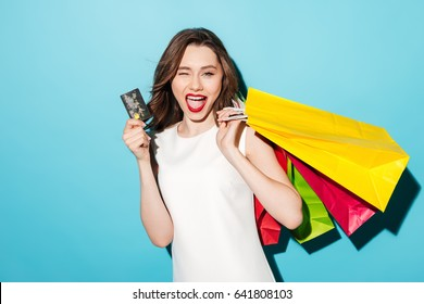 Portrait of a smiling pretty girl in dress with shopping bags holding credit card and winking isolated over blue background