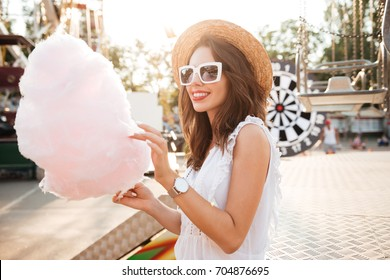 Portrait of a smiling pretty girl in sunglasses holding cotton candy at amusement park