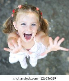 Portrait of smiling pretty little girl with hands up