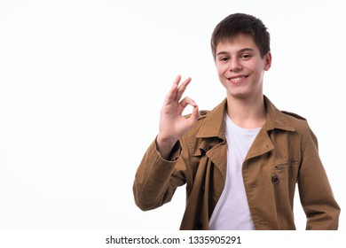 Portrait of a smiling pretty teen boy gesturing ok sign on a white background. The concept of a happy, healthy life. Good luck in all your endeavors.