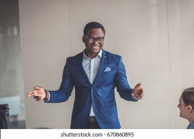 Portrait of smiling pretty young african business man in glasses sitting on workplace