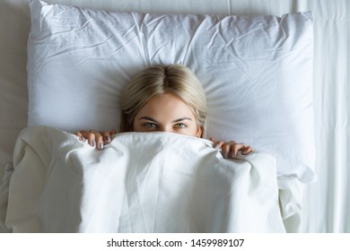 Portrait of a smiling pretty young blonde woman relaxing in white bed.