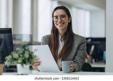 Portrait of smiling pretty young business woman in glasses sitting on workplace and working with documents.