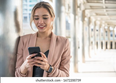 Portrait of smiling pretty young business woman using phone on office background.