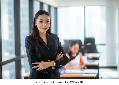 Portrait of smiling pretty young business woman sitting on modern co-working workplace, Start-up office background