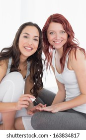 Portrait of a smiling pretty young woman painting friend's nails over white background