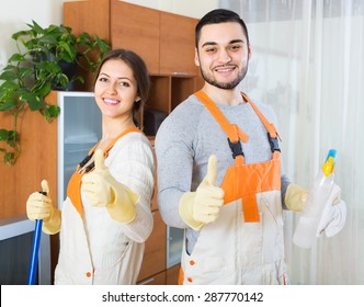 Portrait of smiling professional cleaners team with equipment at client house