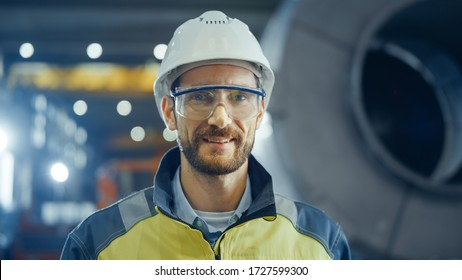 Portrait of Smiling Professional Heavy Industry Engineer / Worker Wearing Safety Uniform, Goggles and Hard Hat. In the Background Unfocused Large Industrial Factory