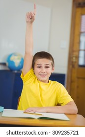 Portrait of smiling pupil raising hand in a classroom in school