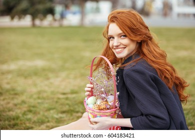 Portrait of a smiling red head girl with long hair holding easter picnic basket with eggs while resting in park