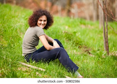 Portrait of a smiling redhead woman sitting in grass