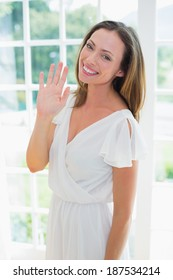 Portrait of a smiling relaxed young woman waving hand at home