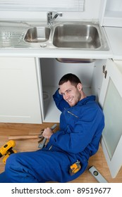 Portrait of a smiling repairman fixing a sink in a kitchen