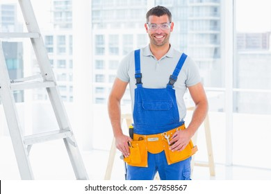 Portrait of smiling repairman in overalls standing hands on hips at bright office