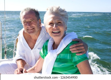 Portrait of smiling retired couple sailing yacht at sea