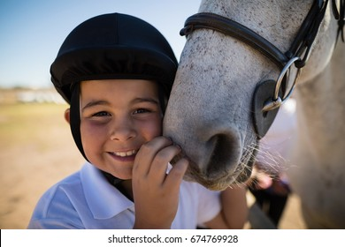 Portrait of smiling rider boy touching the white horse