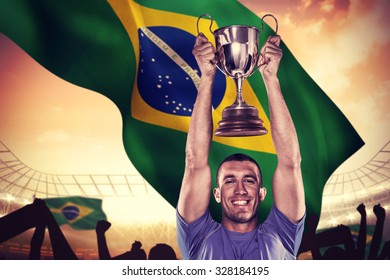 Portrait of smiling rugby player holding trophy against large football stadium under cloudy blue sky