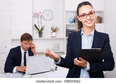 portrait of smiling russian business woman holding cardboard in office
