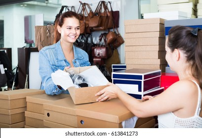 portrait of smiling russian teenage girl talking to seller among boxes with new shoes in fashion store
