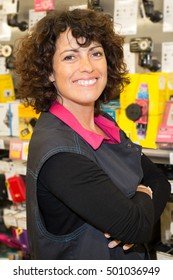 portrait of smiling saleswoman standing and looking at the supermarket with crossing arms
