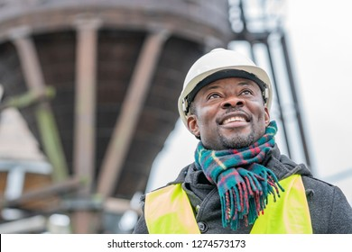 Portrait of a smiling and satisfied African American engineer wearing protective workwear looking upwards on construction site