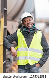 Portrait of a smiling and satisfied African American engineer wearing protective workwear posing on construction site