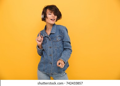 Portrait of a smiling satisfied girl dressed in denim jacket listening to music with headphones while standing with eyes closed isolated over yellow background
