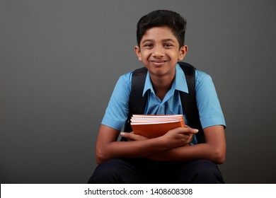 Portrait of smiling school boy  holds notes books in his hands