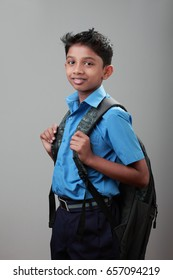 Portrait of a smiling school boy wearing uniform and bag