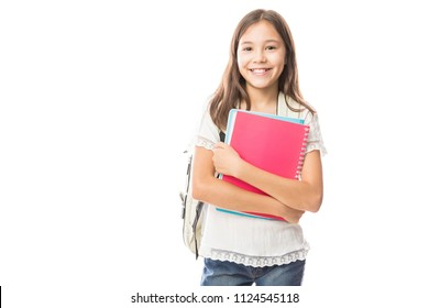 Portrait of smiling school girl child with school bag and books isolated on a white background