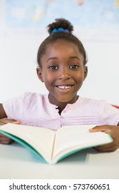 Portrait of smiling school girl reading book in classroom at school