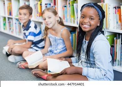 Portrait of smiling school kids sitting on floor and reading book in library