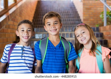 Portrait of smiling school kids standing together on staircase at school