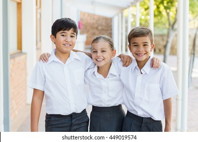 Portrait of smiling school kids standing with arm around in corridor at school