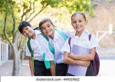 Portrait of smiling school kids standing in campus with books at school