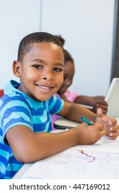 Portrait of smiling schoolboy doing homework in classroom at school