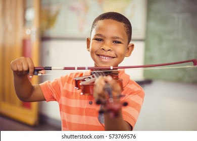 Portrait of smiling schoolboy playing violin in classroom at school
