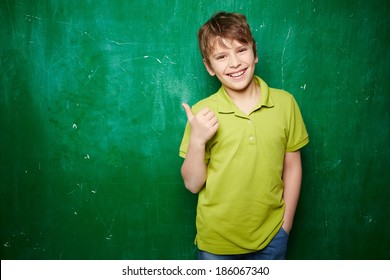 Portrait of smiling schoolboy showing thumb up while standing by the blackboard