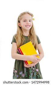 Portrait of smiling schoolgirl with books. Adorable little girl standing holding books. Isolated on a white background
