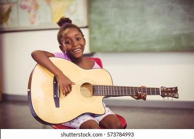 Portrait of smiling schoolgirl playing guitar in classroom at school