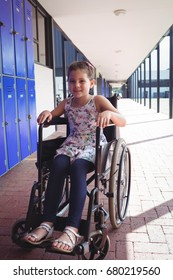 Portrait of smiling schoolgirl sitting on wheelchair in corridor at school